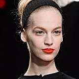 Orange lips have a place in your makeup bag for Autumn, as shown by Nina Ricci's Fall runway.