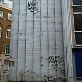 The piece, painted upon a disused building, shows a woman and her shopping free falling.