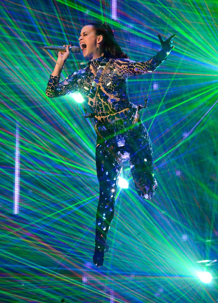 """Katy Perry channelled Sandra Bullock in Gravity at the MTV Europe Music Awards in Amsterdam today, flying high above the audience during her performance of her hit """"Unconditionally."""" The singer pulled the quick change of the night to don her flight suit shortly after she roared onto the black carpet, where she signed autographs and snapped pics with fans. The songstress was without her boyfriend John Mayer at the event, but still played the part of pop princess in an elegant satin mint green dress by Zac Posen for her big night. Katy is nominated for two awards — best female and best pop. Katy promoted her new album, Prism, in Japan last week before heading to Amsterdam to prepare for the EMAs. The singer enjoyed a shopping excursion during a break from her busy pre-EMAs schedule on Saturday, but she is showing no signs of slowing down anytime soon. Katy is gearing up to take her massive hits on the road in early 2014, telling Entertainment Weekly that fans can expect a more mature and """"less cartoony"""" show on her upcoming tour."""