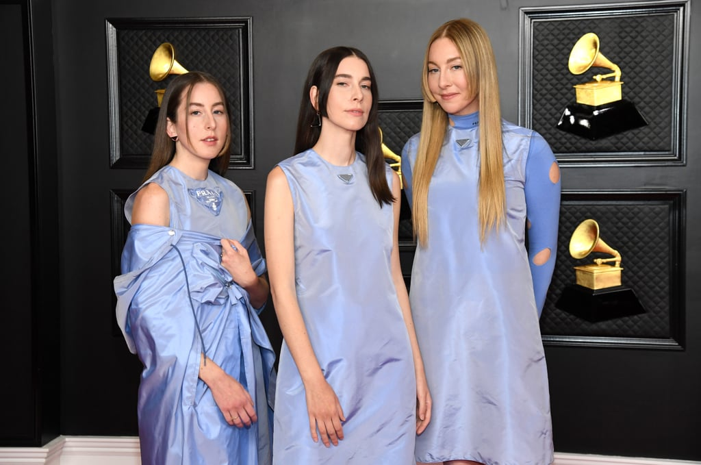 Haim's harmonious appearance at the 2021 Grammy Awards seemed ripped right out of the pages of a '90s fashion magazine. The rock group — consisting of sisters Este, Danielle, and Alana Haim — attended the award show wearing custom, periwinkle Prada outfits in a nylon material typically associated with the brand's iconic backpacks.  Though the trio was sartorially in sync, each sister had a distinct look: Danielle wore a shift dress over trousers, Este's dress was layered over a cutout turtleneck, and Alana wore a sleeveless top, trousers, and off-the-shoulder parka. All three accessorised with Prada earrings and pointed-toe flats in the same blue shade. Take a closer look ahead.      Related:                                                                                                           How Gorgeous Does Taylor Swift Look in Her Flower-Covered Grammys Dress?