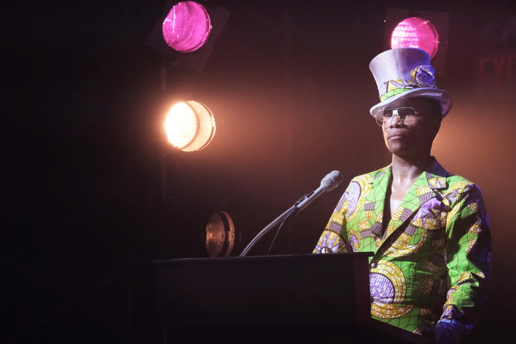 Wearing an eye-catching green printed suit. It's hard to miss his matching lavender top hat.
