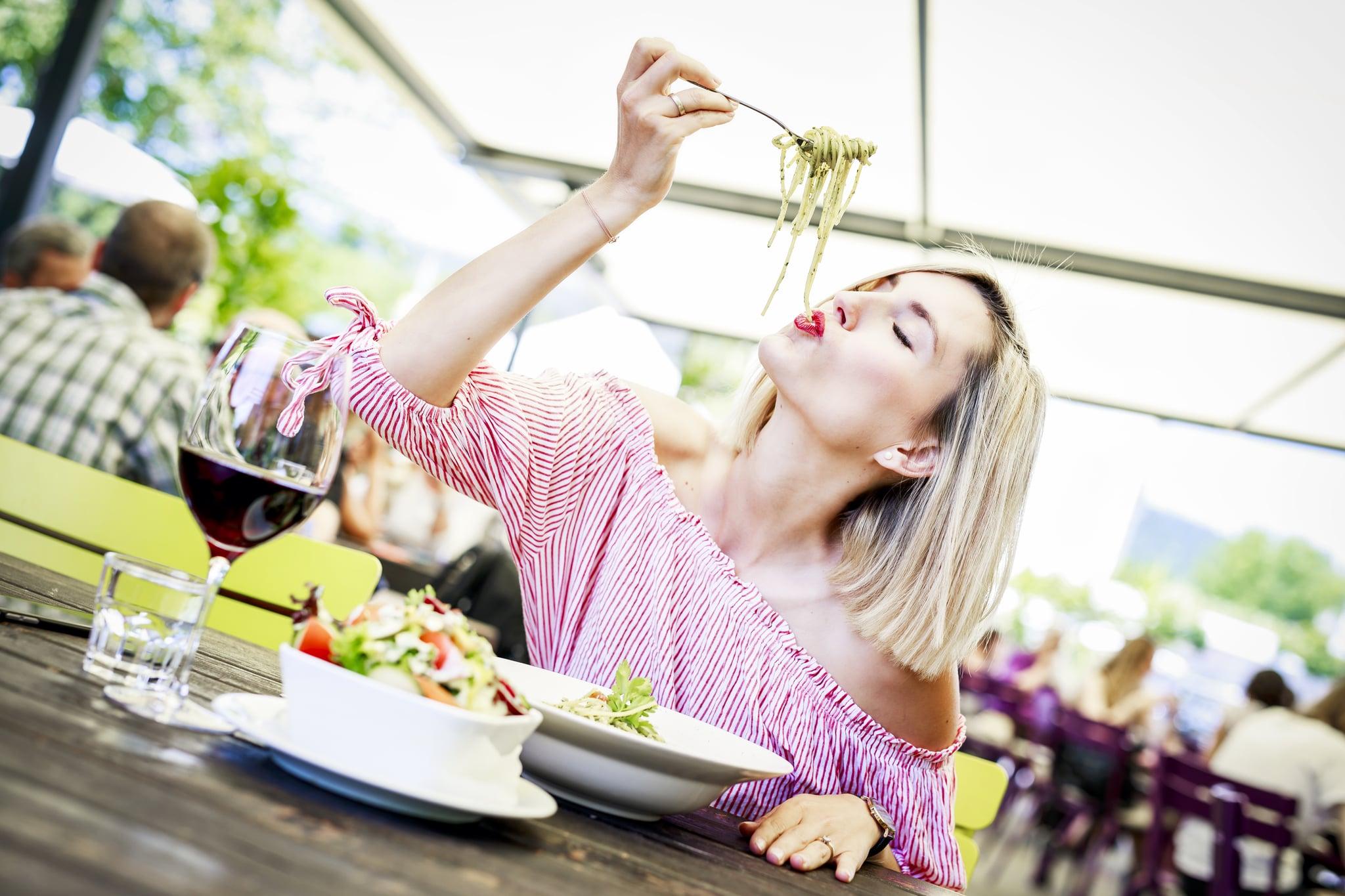 Junge Frau isst Spaghetti in einem Gastgarten