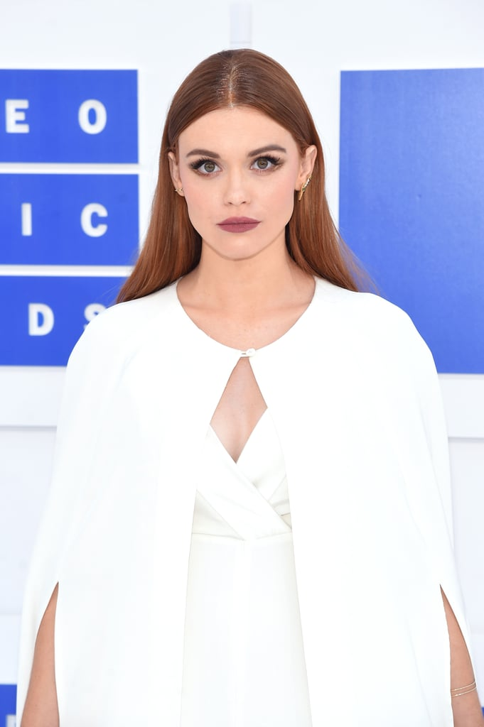 Well, this is exciting! Glitter roots — which were perhaps once considered a niche beauty trend — have officially made their way onto the MTV Video Music Awards red carpet at Madison Square Garden. Teen Wolf star Holland Roden sported the trend while wearing an all-white jumpsuit and cape. From the looks of her preshow Instagram, it appears that Holland's glitter roots are in a subtle (yet stunning) bronze shade. Since Holland's incredibly chic ensemble was pretty minimalistic, we have to say that glitter roots were the perfect finishing touch. (But we pretty much always think that.)      Related:                                                                Women Are Now Hiding Their Grown-Out Roots With Glitter                                                                   Miley Cyrus Will Inspire You to Finally Embrace the Glitter Roots Trend