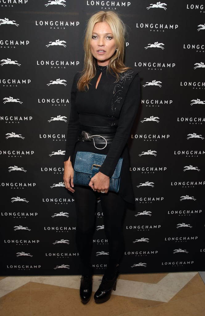 Kate Moss stuck to her signature black — albeit with pop of blue — at the Longchamp store opening during London Fashion Week.