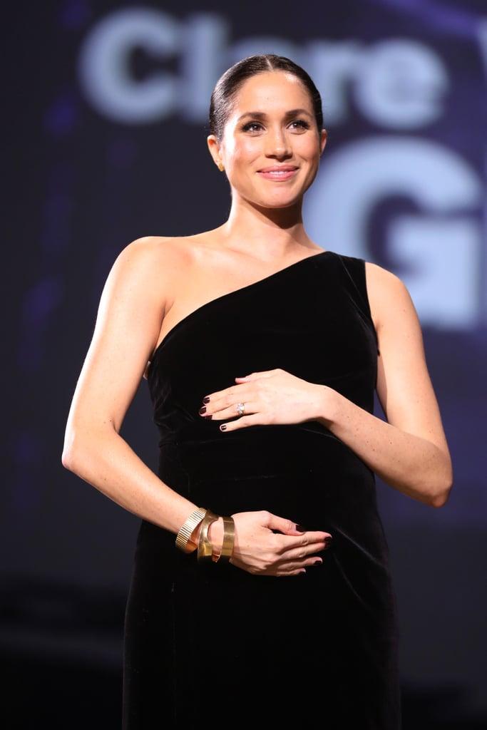 """ظهرت ميغان ماركل بشكلٍ مفاجئ يوم الاثنين عندما أطلّت بحفل جوائز الأزياء البريطانيّة لعام 2018 في لندن. وقد كانت دوقة ساسكس –التي تنتظر قدوم طفلها الأول من الأمير هاري في الربيع المقبل– متألّقة جدّاً بفستان أسود ذو كتف واحد في حين راحت تحتضن بين ذراعيها بطنها الآخذ بالانتفاخ على خشبة المسرح وذلك خلال تقديمها جائزة أفضل مصمّم بريطانيّ لهذا العام للمصمّمة """"كلير رايت كيلر"""" المديرة الإبداعيّة لعلامة جيفنشي. لكن ورغم أنّ مشاركة ميغان لم تكن متوقّعة إطلاقاً، لا نستغرب كثيراً قيام النّجمة الملكيّة هذه بتقديم تلك الجائزة المرموقة للسيدة كلير؛ فهي التي صمّمت لها فستان زفافها. يأتي الظهور الآسر لميغان ذاك بعد أقل من أسبوع من قيامها بزيارة سريّة إلى كليّة الملك في لندن بغية حضور اجتماع لرابطة جامعات الكومنولث. خلال ذلك اللّقاء، ناقشت ميغان دور الجامعات في معالجة قضايا مثل الاتّجار بالبشر، والعبوديّة الحديثة، والمساواة والشموليّة بين الجنسين، والسلام والمصالحة، وتغيّر المناخ، والصمود في وجه الصعاب. شاهدوا أدناه جميع الصور الساحرة التي سلّطت الضوء على ميغان ماركل في أحدث إطلالة لها!"""