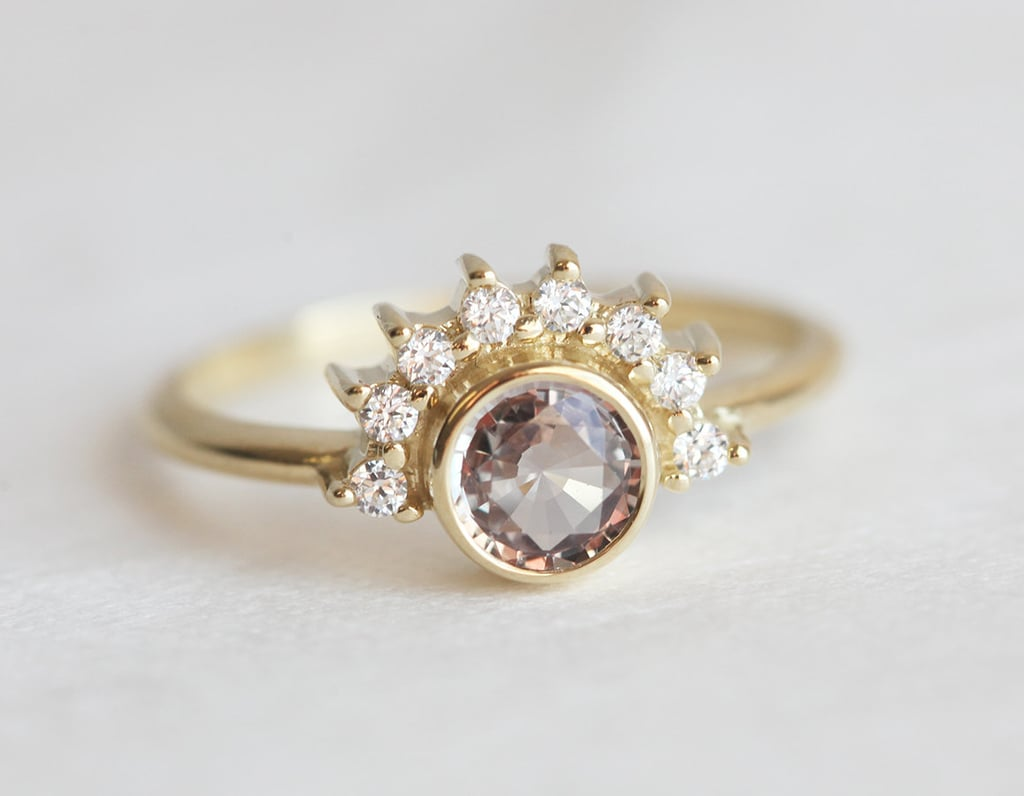 The half-moon diamonds surrounding the peach sapphire on this ring ($1,580) givee it a unique feel.
