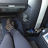 Here's a look at the spacious legroom with the seat in an upright position. With the buttons on the armrest, you're able to adjust how far back you want the seat to recline (including a full lie-flat option), the firmness of the cushions, and the massage feature. That said, I couldn't really tell the difference between the massage and just the normal vibrations of the plane. But the leg room and reclined seats were incredible. Not pictured: the tray table comes from the center divider (on my right) instead of pulling down from the back of the seat in front of you. Mine happened to be very slanted and close to my body, which made being on my computer and eating a little bit awkward.