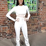 Winnie Harlow masters the art of the high-waist pant with a sheer layer and a fierce pair of boots.