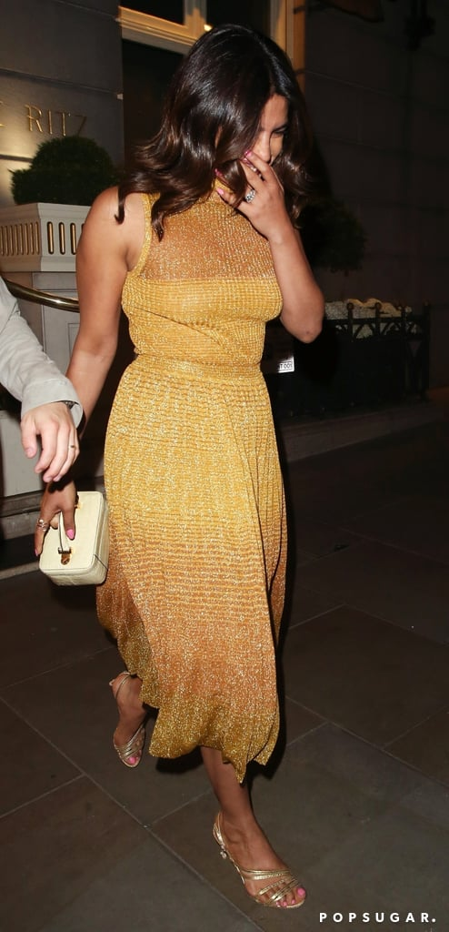 Priyanka Chopra was absolutely glowing during a recent outing with Nick Jonas in London. It also didn't hurt that she was wearing head-to-toe gold. On the couple's ongoing romantic European vacation following Joe Jonas and Sophie Turner's wedding in the French countryside, the actress looked stunning as she stepped out wearing a matching Ulla Johnson top and skirt in a dazzling metallic fabric.  Priyanka accessorized her outfit with strappy gold Alexandre Birman heels and a boxy cosmetic case handbag by Stalvey. Her date, meanwhile, also wore a monochromatic outfit consisting of a navy mesh — mesh! – shirt from Mr Turk and navy trousers. Nick also wore a gray suede jacket, a leather pouch, and quintessential dad sneakers by New Balance. Though the shimmery fabric and sleeveless silhouette of Priyanka's matching set make for a fun Summer party look, we also can't help but feel like she may have just given us the inspiration we need for our next New Year's Eve outfit. (Hey, it's never too early to start planning!) Though her exact top doesn't appear to be currently available online, Ulla Johnson offers a long-sleeved top in the same material. Shop Priyanka's exact skirt and other similar metallic numbers ahead.      Related:                                                                                                           Priyanka Chopra's Plunging Swimsuit Is So Sexy, It Has Sophie Turner's Seal of Approval
