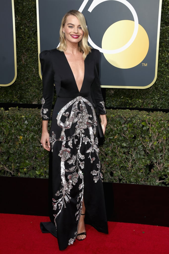 Margot Robbie wearing a Gucci dress with a clutch and shoes by Roger Vivier and Tiffany & Co. jewels in 2018.