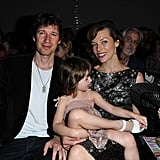 Milla Jovovich held her daughter, Ever Anderson, in her lap and had Paul W.S. Anderson by her side at the Jean Paul Gaultier show.