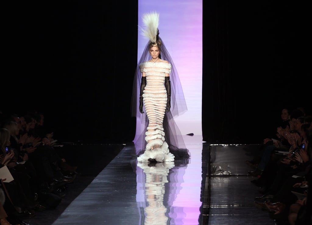 ">> Despite the fact that his Spring 2011 couture show was inspired by the English punk rock movement and the French can can, Jean Paul Gaultier didn't play any musical soundtrack. Instead, the models paraded in their mohawks and their individual outfits — named things like ""The Clash,"" ""Belle Epoque,"" ""Anarchy in the UK,"" and ""Moulin Rouge"" — carrying a number in the old school couture way, with Catherine Deneuve calling out the number and then describing the looks in a voiceover. The show, which started over an hour late, culminated in the androgynous male model Andrej Pejic — Gaultier's new favorite — appearing as couture bride in a semi-sheer gown. As the model parade ended, Gaultier finally let the music loose, unleashing a Crazy Horse can can dancer to do splits and kicks down the runway to Offenbach as Deneuve and Pedro Almodovar cheered. The designer took his bow with Farida Khelfa, who walked and also recently completed a documentary on him. Backstage, Jeanne Beker reports, Gaultier said he ""has disdain for the red carpet. Loved seeing Marion Cotillard in his mermaid dress [at the 2008 Oscars] BUT.....He wonders why some houses actually PAY actresses to wear their dresses. And he misses CHER!"""