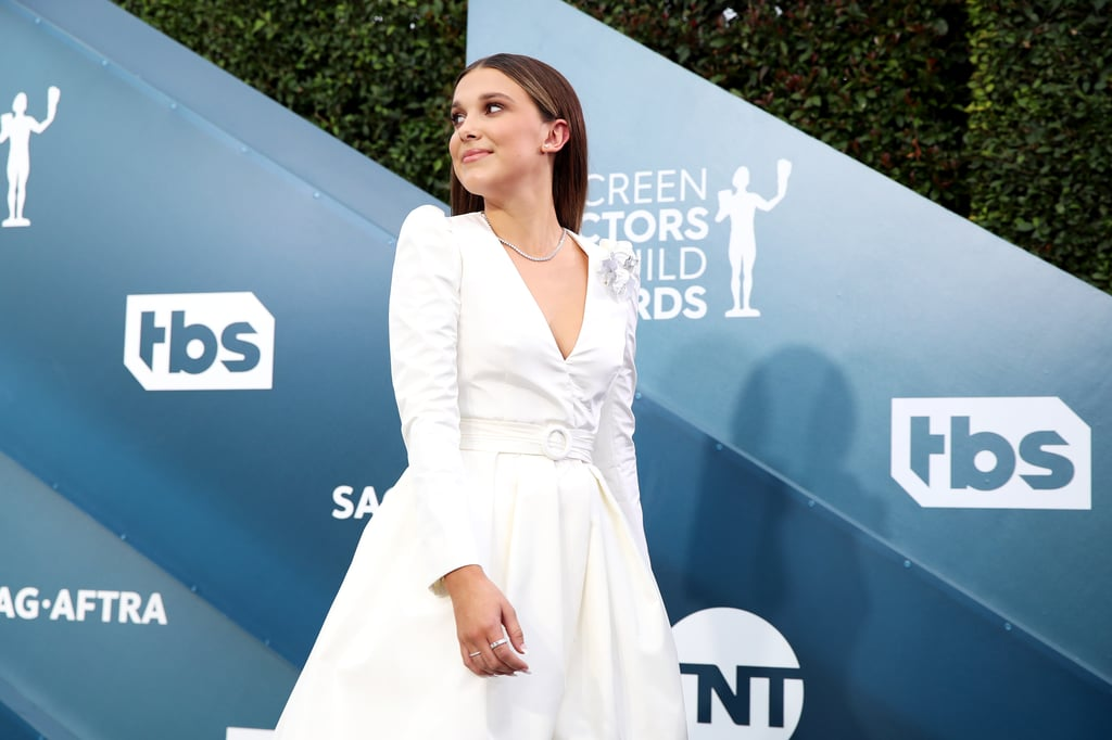Millie Bobby Brown redefined the skirt suit at the 2020 SAG Awards. The Stranger Things actress attended the star-studded award show on Jan. 19 wearing a custom-made Louis Vuitton outfit consisting of tailored trousers and a high-low, belted dress jacket featuring a modern boutonnière.  Styled by Thomas Carter Phillips, the outfit was complemented by satin, pointed-toe pumps also by Louis Vuitton and a casual amount of Cartier jewelry, including a diamond necklace, earrings, and several rings. Get a closer look at Millie's classic and crisp outfit ahead, and then check out photos of Millie hanging with her Stranger Things costars on the red carpet.      Related:                                                                                                           In Case You Missed It, We've Got All the Best SAG Awards Looks Right Here