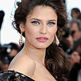 Bianca Balti accessorized with gold statement earrings and a side-swept ponytail.