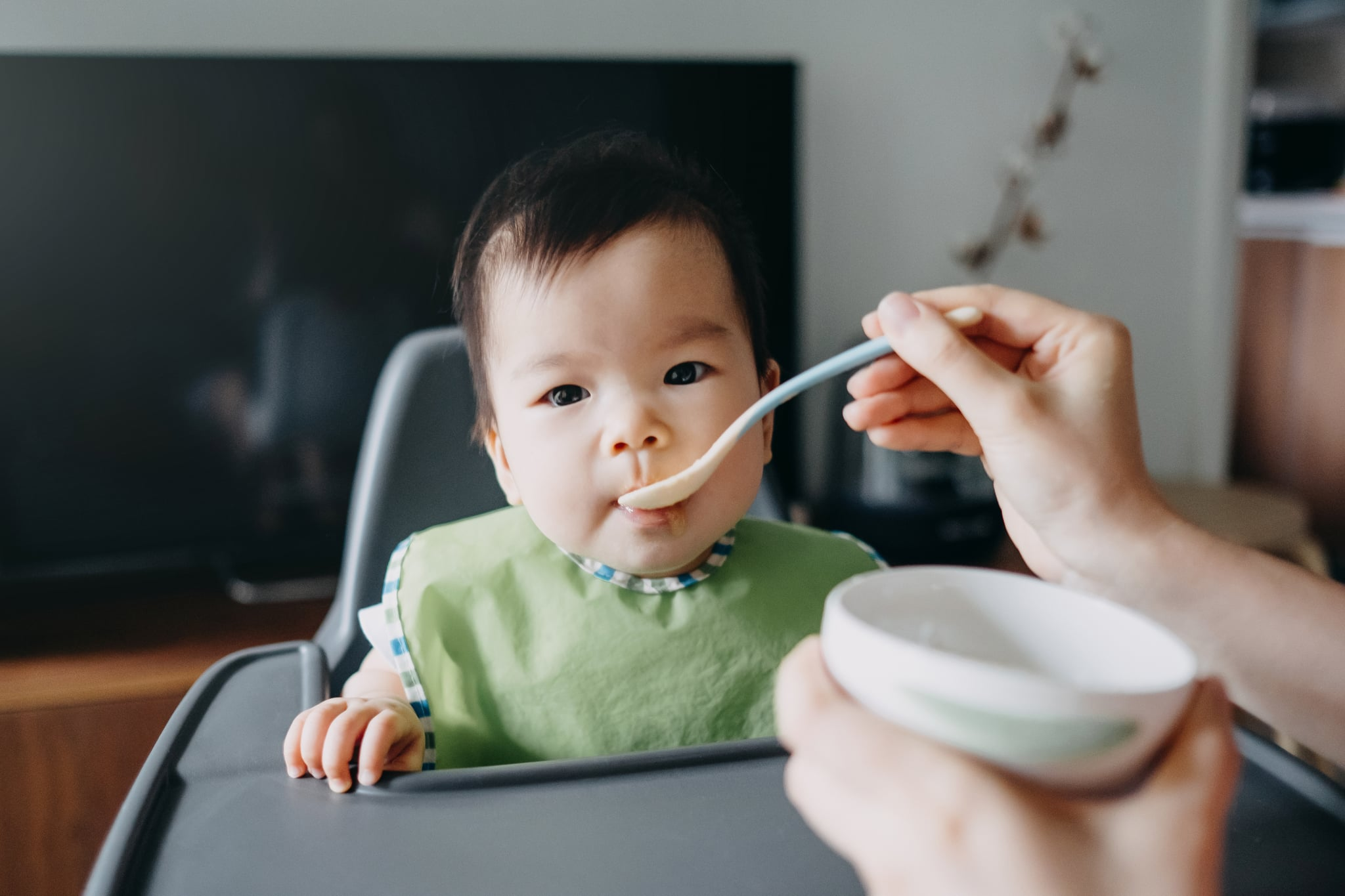 Mother's hand feeding baby girl food on high chair at home