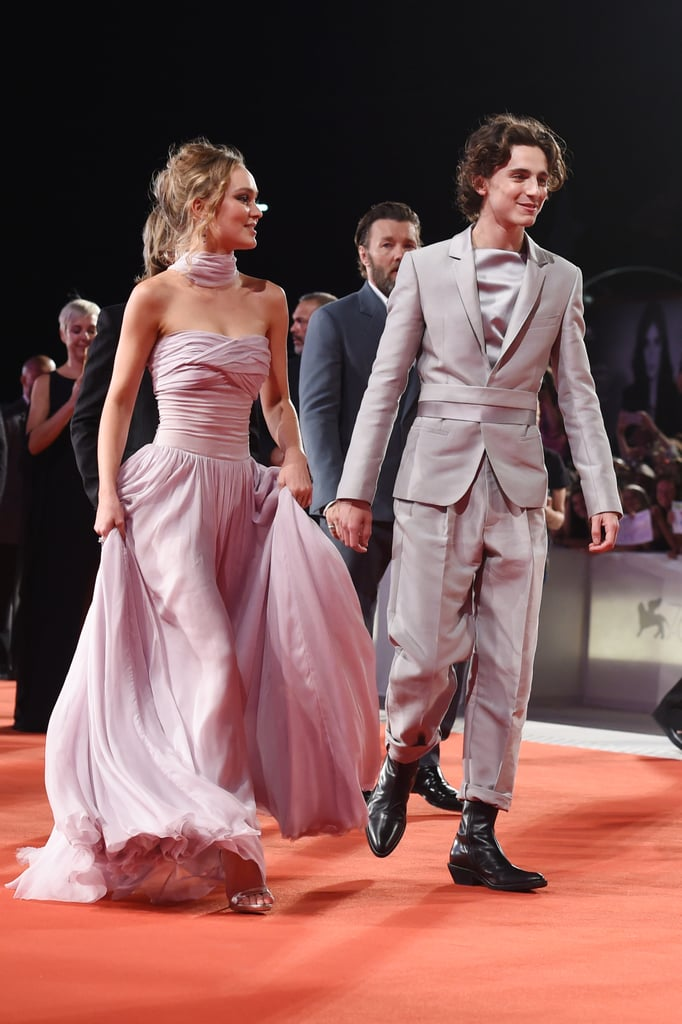 Timothée Chalamet and Lily-Rose Depp's glamorous appearance at The King world premiere will leave you bowing down — and I'm not just saying that because of the convenient pun. Wearing complementary gray outfits, the costars celebrated their forthcoming Netflix film at the 2019 Venice Film Festival on Monday. Though Timothée and Lily were reportedly dating as of Oct. 2018, the two appeared to keep it strictly professional on the red carpet. Timothée and Lily, who portray Henry V and Catherine of Valois in the film, were joined by their costars Joel Edgerton, Ben Mendelsohn, Tom Glynn-Carney, Sean Harris, and director David Michod. Fortunately Robert Pattinson, who portrays Louis, Duke of Guyenne, was unable to attend, for that might have been too much to handle. See the royally stunning shots of Timothée and Lily ahead.
