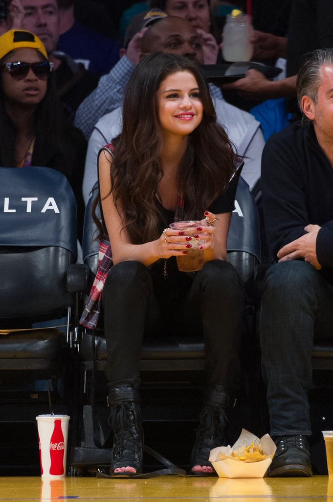 At a March Lakers game, Selena Gomez worked plaid in an edgy way by pairing her sleeveless top with all black, including lace-up, peep-toe booties.