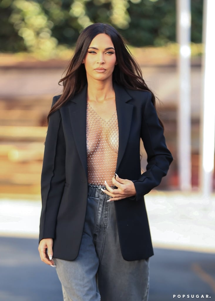 Megan Fox's sexy style reign continues. Whether she's walking the red carpet or casually strutting the streets with boyfriend Machine Gun Kelly, Megan consistently chooses looks that leave us breathless. She can wear Mugler one day and a casual crop top on another; her instincts know what works. Take her recent photo-shoot outfit, for example.  On June 11, Megan was spotted leaving an LA project in a structured blazer, slouchy black jeans, a barely there rhinestone mesh top, and Alexandre Birman heels. We've never seen business casual quite like this! She tied the whole look together with jeweled heels, turning the parking lot into her personal runway. Get a closer look at her full ensemble ahead.       Related:                                                                                                           Megan Fox and Machine Gun Kelly's Romance Just Keeps Getting Cuter and Cuter