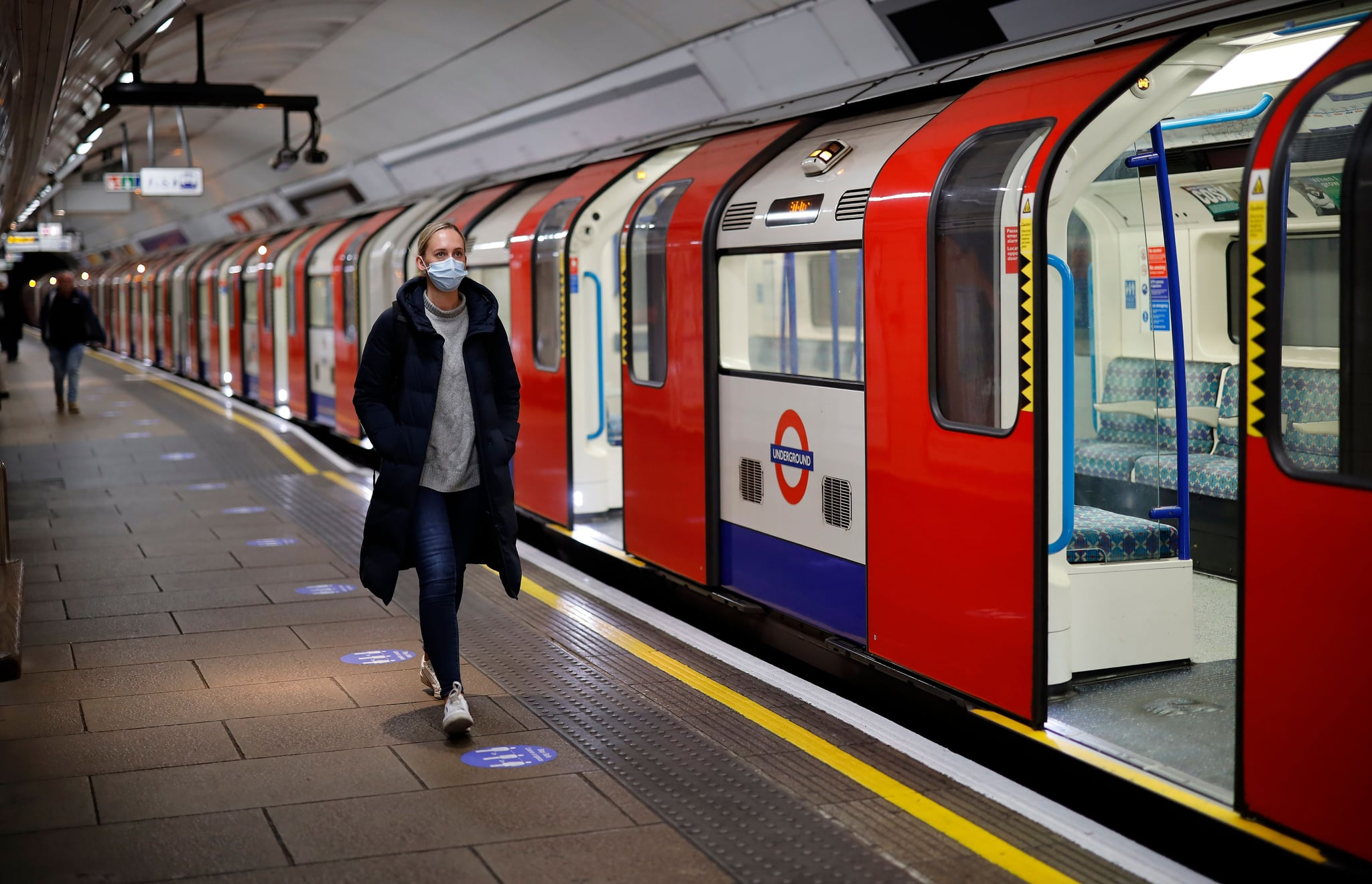 A woman wearing PPE (personal protective equipment), including a face mask as a precautionary measure against COVID-19, walks along the platform alongside a London Underground Tube train in the morning rush hour, on May 11, 2020, as life in Britain continues during the nationwide lockdown due to the novel coronavirus pandemic. - British Prime Minister Boris Johnson on May 10 announced a phased plan to ease a nationwide coronavirus lockdown, with schools and shops to begin opening from June 1 -- as long as infection rates stay low. (Photo by Tolga Akmen / AFP) (Photo by TOLGA AKMEN/AFP via Getty Images)