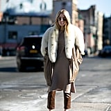 With a Long Neutral-Colored Shirt, a Furry Jacket, and Neutral Slip-On Shoes