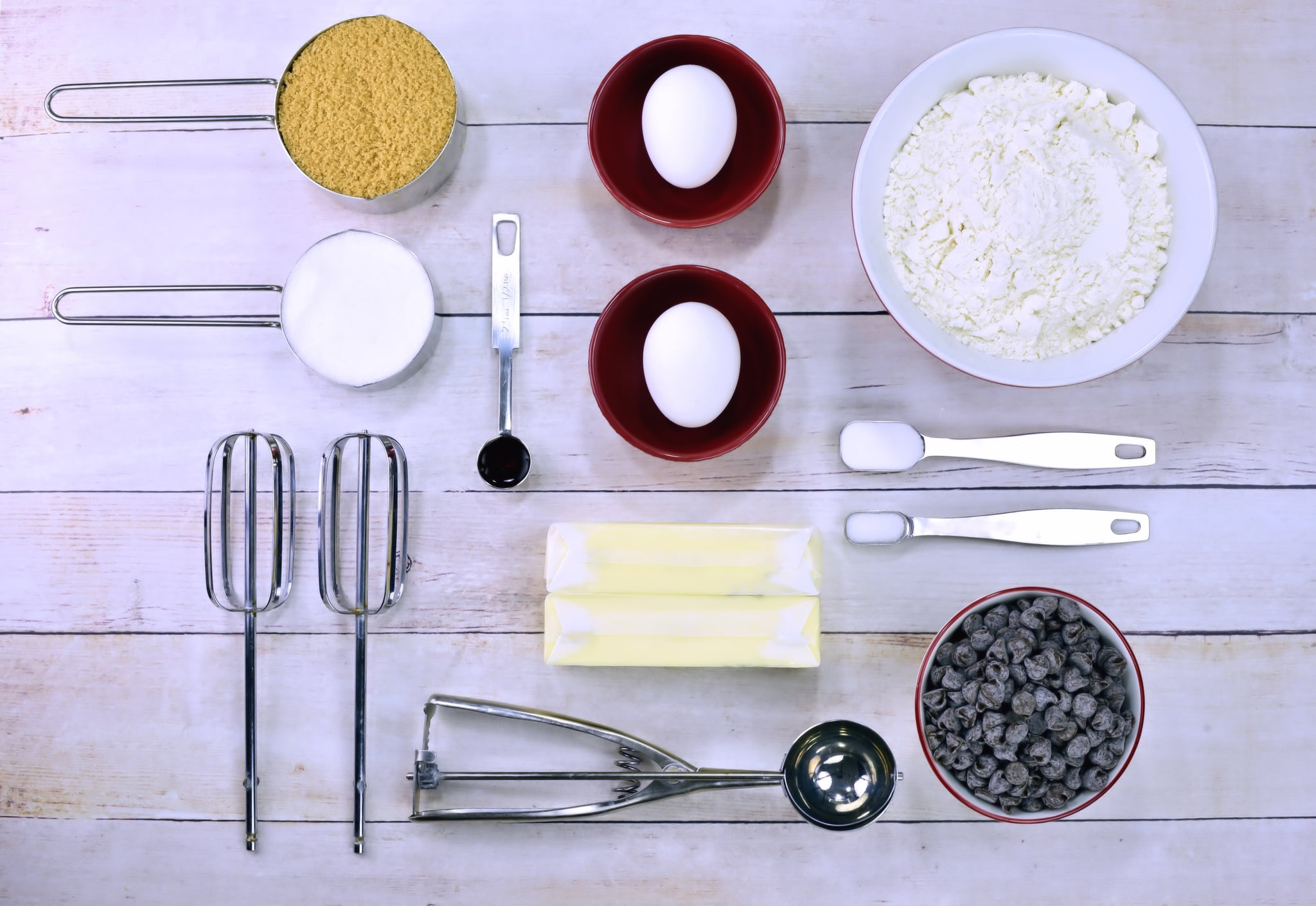 All of the ingredients to make chocolate chip cookies including sugar, flour, butter, eggs and chocolate chips