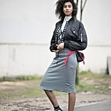 With a High-Neck Top, a Bomber Jacket, a Midi Skirt, and Fishnet Tights