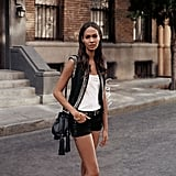 Joan Smalls styled her lace-up denim shorts with a punchier vest on top, which is a perfect daytime combination. For nighttime? Try pairing the vest with a longer black maxi dress and ankle boots.