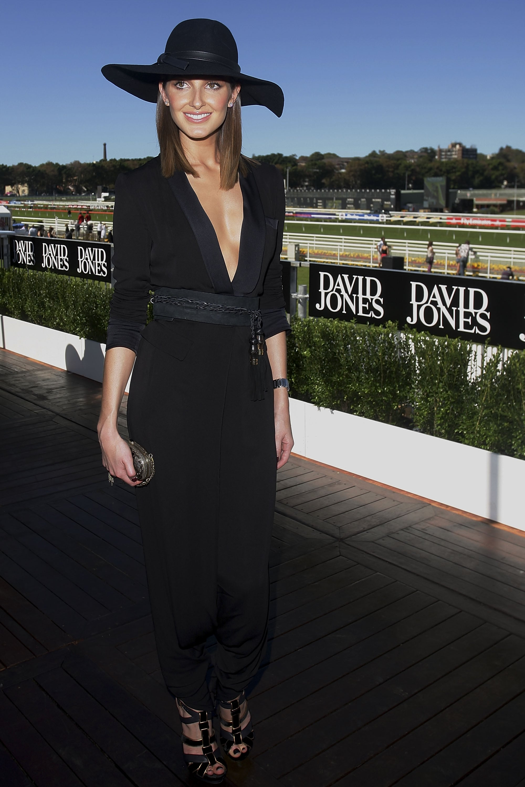 Kate Waterhouse looked extra chic in a plunging black jumpsuit and white brimmed hat. Modern but alluring!