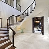 There is a grand entryway with a sweeping staircase.