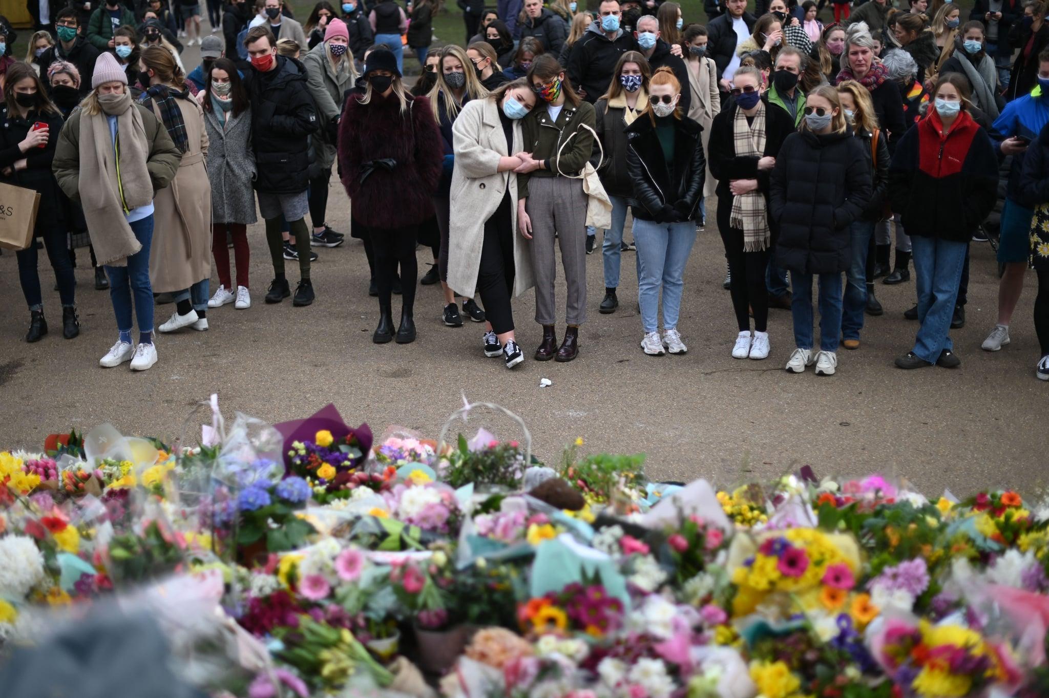 خیرخواهان هنگام تجلیل از ادای احترام به گل سارا اورارد ، زن گمشده ای که در جبهه های جنگلی در کنت ، در تابلوی بند در Clapham Common در جنوب لندن در 14 مارس 2021 پیدا شد ، افراد خیرخواه واکنش نشان می دهند - پلیس متروپولیتن لندن در 14 مارس دفاع کرد پس از مشاهده افسران مردی که با جمعیت درگیر شده بودند و تظاهرکنندگان زن را از نظر جسمی منع می کردند ، این کار با اعتراض پر سر و صدا خواستار افزایش امنیت عمومی برای زنان بود.  صدها نفر از محدودیت های ویروس کرونا در 13 مارس شب برای تجمع در پارک کلپام مشترک به نشانه مرگ سارا اورارد ، که در همان اوایل ماه هنگام رفتن به خانه به خانه گم شد ، ناپدید شدند.  از آن زمان یک افسر پلیس در حال خدمت با نیروهای لندن به آدم ربایی و قتل متهم شد.  (عکس از DANIEL LEAL-OLIVAS / AFP) (عکس توسط DANIEL LEAL-OLIVAS / AFP از طریق گتی ایماژ)