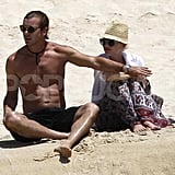 Shirtless Gavin Rossdale covered bikini-clad Gwen Stefani.