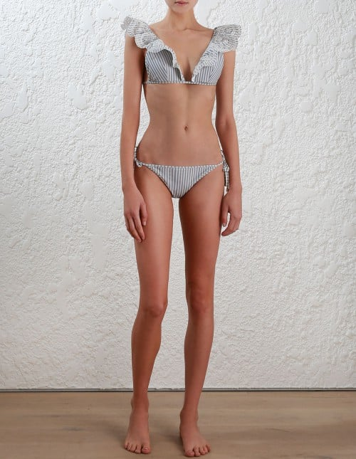 If you love frills and ruffles, opt for a style where the details are up top and pair it with a simple, matching bottom. We're all about Zimmermann's Meridian Stripe Tri Bikini ($315).