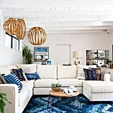 Jamie told us that the living room was in need of some pops of color, better lighting, and a new couch. Decorist did not disappoint, bringing in a beautiful white sectional, vibrant blue rug, and some seriously unique pendant lights.