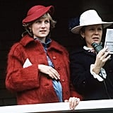 Princess Diana attended the Grand National Race Aintree while she was pregnant with Harry back in 1984. Her outfit of choice? A warm maroon coat with a matching saucer hat over a blue high-collared frock and a dainty clutch tucked under her arm.