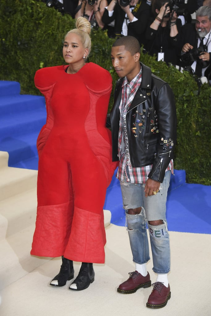 "Although Pharrell Williams is one of the Met Gala co-hosts this year, his wife, Helen Lasichanh, totally stole the spotlight on the red carpet. When the couple arrived, our jaws dropped at her over-the-top look: a voluminous bright-red jumpsuit of sorts with no apparent armholes (which made for some semi-awkward poses and quite the plethora of entertaining internet reactions). We've gotta hand it to her — she really stuck to the avant-garde theme of the evening, which is an ode to Comme des Garçons designer Rei Kawakubo.  Meanwhile Pharrell was chillin' in a plaid buttondown shirt, leather jacket, and ripped jeans, which seems a tad casual for the occasion. But hey, he did attach a handful of cool acrylic pins to his leather jacket; plus he had ""REI"" stitched on one knee of his jeans as a tribute to the famed designer, so we'll give him an A for effort. Read on to see the interesting juxtaposition between the couple's Met Gala outfit choices."