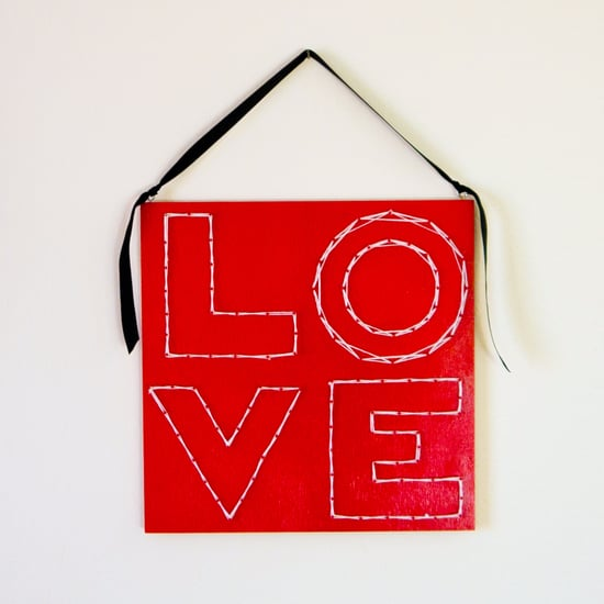 Get Crafty: Valentine's Day String-Art Wall Hanging 11/23/161/29/13POPSUGARLivingValentine's DayValentine's Day DIY String ArtGet Crafty: Valentine's Day String-Art Wall Hanging January 29, 2013 by Sarah Lipoff2 Shares Spread your love around on Valentine's Day with this totally mod string-art wall hanging that's easier to make than you think. With the help of nails, a board, and a bit of red spray paint, you're on your way to a really chic-looking piece of art that will brighten your home or make a really special gift for someone special. And this DIY costs around $10 to make, making it as reasonably priced as a deluxe box of chocolates — but much more personal. What You'll Need:12-by-12-1/4-inch birch plywoodRulerPencilSmall bowls or round containersMagazines1/2-inch wire nailsHammerRed spray paintWhite yarnEye hooks (optional)Ribbon (optional)Directions:Gather your materials and think about how you'd like your big letters to look. You can write the letters in cursive or large block letters like I did. If - 웹