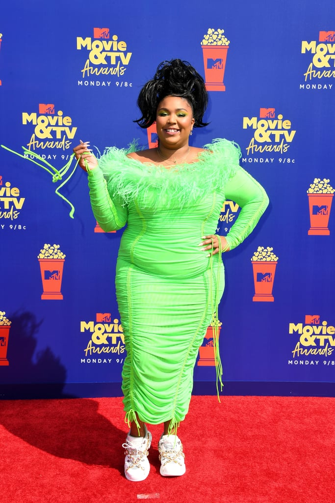 Lizzo legitimately looked like she was having the most fun at the 2019 MTV Movie & TV Awards. How can you not though when you're wearing a blindingly bright neon green dress? A month after appearing at the Met Gala in a show-stopping Marc Jacobs gown — which she wore to the airport the following day, by the way — the singer attended the award show in a custom Christopher John Rogers dress that embodied all the trends with its ruching and feathered neckline. Lizzo completed the look with jewel-adorned chunky sneakers.  The look was spot-on for such a fun night. Not only that, but upon realising that her dress kind of resembled a green screen, Lizzo delivered a truly hilarious meme. Love that versatility! Enjoy photos of Lizzo living it up on the red carpet ahead.      Related:                                                                                                           The MTV Movie & TV Awards Red Carpet Will Bring More Colour to Your Week