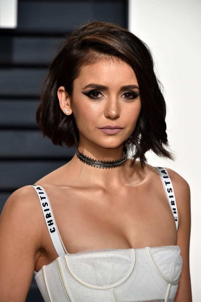 "When Nina Dobrev stepped foot on the red carpet at the 2017 Vanity Fair Oscars party, we immediately fell in love with her new haircut. The Vampire Diaries actress debuted an even shorter, A-line bob after her drastic chop just six weeks ago, captivating us with total Victoria Beckham vibes. Nina's BFF and hairstylist Riawna Capri got to work cutting Nina's hair even shorter ""using texturizing techniques"" and styling it with three different-size curling irons to create the perfect natural-looking 'do. But once we zoomed in on her flawless dewy glow, it was Nina's makeup that stole the show.   Nina's classic, Audrey Hepburn-inspired hairdo was taken to new grungy heights with the help of a sultry cat eyeliner and a matte pink lip. Celebrity makeup artist Spencer Barnes teamed up with E.L.F. Cosmetics to give Nina the ultimate shimmering look.  ""I kept Nina's skin fresh, flawless, and soft and honed in on dramatic brows and lashes,"" Spencer said. Using only E.L.F. products, each ranging from $3-$12, Nina's look was both stunning and totally affordable.      Related:                                                                                                           98 Reasons Birthday Girl Nina Dobrev Is Our Ultimate Style Crush               The most underrated part of Nina's look, however, was her pout. Spencer used a rose-colored eye shadow to create the kissable and ""ultra-matte nude finish."" The E.L.F. Beautifully Bare Matte Eye Shadow in Blushing Rose ($4) brought the entire look together in an unexpected and elegant way.  Keep reading to see photos of Nina's gorgeous Oscars look and some of the products used to achieve her red carpet glow."