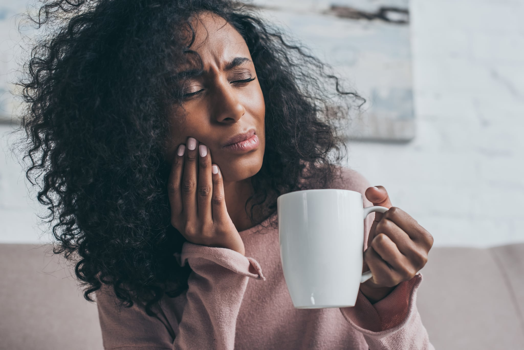 unhappy african american woman suffering from toothache and holding coffee cup