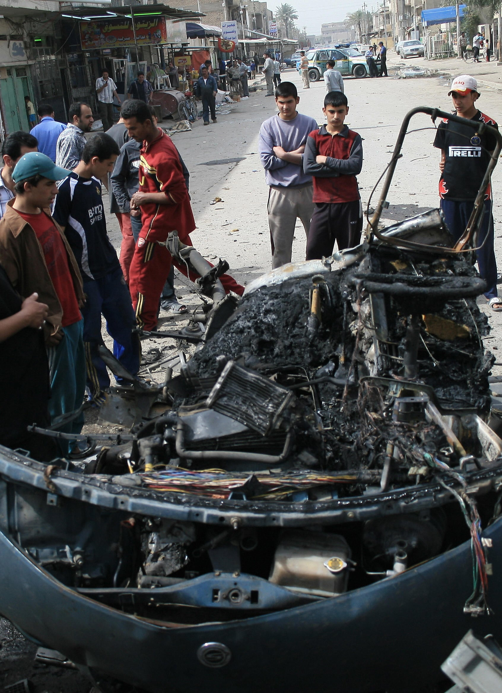 Iraqi youths gather around the wreckage of a car at the scene of an explosion in Baghdad's Al-Shaab neighborhood on Mar 10, 2007