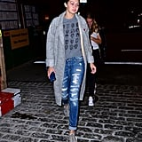 Wearing distressed denim with a graphic tee, gray jacket, and Yeezy sneakers.