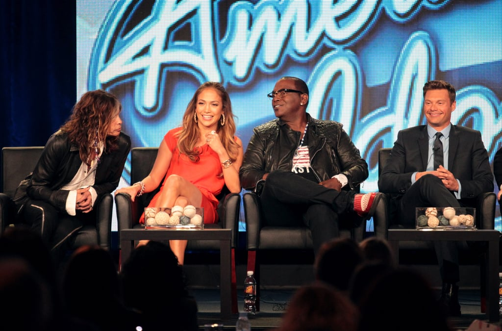 "Jennifer Lopez joined Steven Tyler, Randy Jackson, Ryan Seacrest, and their producers for yesterday's American Idol panel at the Television Critics Association Fox press day. When Jennifer was asked what dress she was wearing, Ryan was quick to interject saying the right question is, ""Who are you wearing?"" though she still couldn't remember the answer. Earlier in the morning, the Fox executive panel addressed the stories about Ryan leaving the show, but he was there with a smile on his face alongside the three judges. Ryan also spoke to the rumors, saying he can't imagine leaving Idol. Ryan is fresh off a St. Barts vacation with bikini-clad girlfriend Julianne Hough and has a perfect tan to kick off award season red carpets this week. Jennifer, Steven, and Randy weren't afraid to throw a few punches at the other singing reality competition shows out there, especially The Voice. The Fox president in charge of American Idol even called out The Voice for having Kelly Clarkson on as a coach this season, saying, ""It's a compliment to Idol because we have created the superstar. We're not hiring a lot of people from The Voice to be on our show."" Check out the 10 best quotes from American Idol's TCA panel on Buzz."