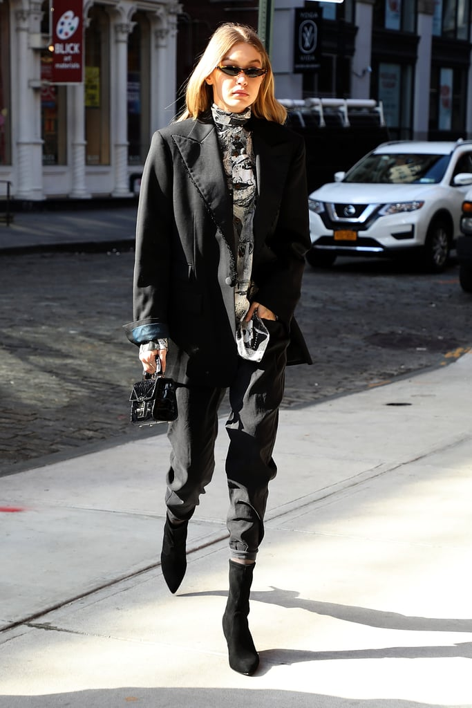 The model took a menswear-inspired approach to Fashion Week dressing in this black ensemble. Gigi wore a printed button-down shirt with an oversize blazer jacket and slouchy jeans. She cuffed them just a little to reveal her black Stuart Weitzman sock booties.