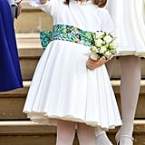Princess Charlotte was seen in a white dress with a colourful belt detail as she attended Princess Eugenie's wedding in 2018.