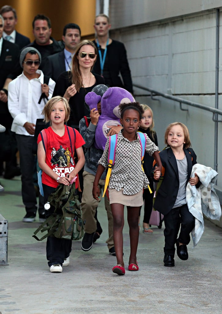 Sydney got a massive boost of Hollywood star power this morning when Angelina Jolie landed at Sydney Airport with her six children in tow. The actress is reported to be staying here for about three months to direct her next feature, a World War II drama called Unbroken; she made a super-quick stop in Australia in late July that lasted less than 24 hours to do some location scouting. Her partner Brad Pitt did not join the family as he's filming Fury in England, which also happens to be a drama about World War II. The Jolie-Pitt kids looked chirpy for their 6:10 a.m. arrival and walked ahead of their mother as they left the airport via a special exit. Zahara and Knox led the pack holding hands, with Shiloh not far behind and Pax hiding behind the big purple plush toy he's carried all around the world on the family's travels. Vivienne stayed close to Angelina while eldest son Maddox, in a beanie and sunnies, rounded the family out. They headed straight to their hotel but are reported to be staying in Sydney's eastern suburbs for the duration of their stay.