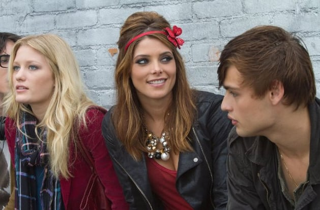 Ashley Greene in a funky outfit including a red floral headband and a statement necklace with pearls.