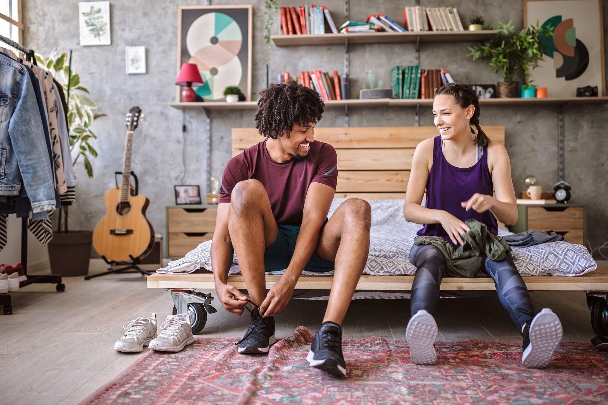 Attractive woman and handsome Afro man sitting on bed, tying shoelaces before morning jogging