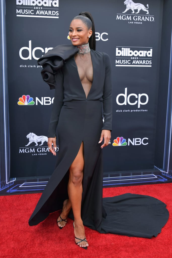The Billboard Music Awards red carpet definitely wasn't short of sexy looks, and one star who really turned up the heat was Ciara. Her Stephane Rolland gown, a modified style from the Fall 2018 collection, featured a dramatic thigh-high split and a deep plunging neckline with a sheer panel and a built-in crystal embellished choker. All this was finished with a giant billowing bow/flower on the shoulder for a little added drama. Between the showstopping gown and her adorable date (her son, Future) you'd be forgiven for missing the little details . . . but even with all that going on, we found ourselves looking down to her feet. Though Ciara's gown may have been couture, her shoes were much more affordable. She chose the Donatella Mule from Femme Shoes, which can be yours for $139. They're vegan and cruelty-free, and as you can see on Ciara, they definitely make an impression. That said, with a superhigh stiletto heel and only thin crossover straps to keep them on the feet, these mules aren't for the faint hearted, and needless to say the singer swapped them out before embarking on an incredible performance. Keep reading to see how Ciara made them work for the red carpet, and to shop a pair for yourself.