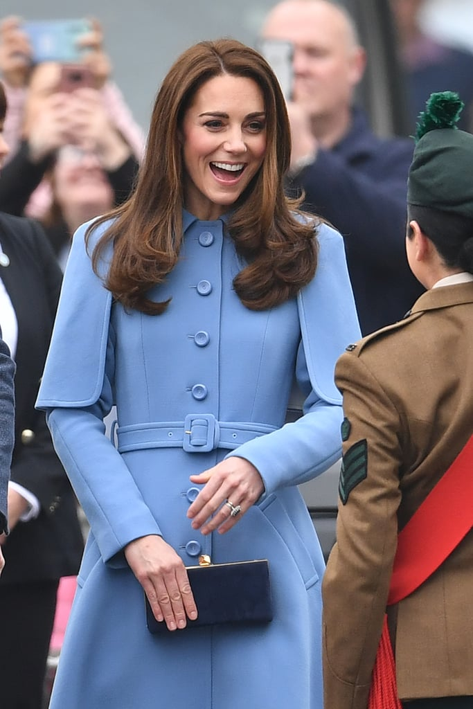 As the Duke and Duchess of Cambridge stepped out for the second day of their trip to Northern Ireland, Kate made us gasp as she debuted a stunning new coat. The duchess has always had an enviable outerwear collection, but this blue Mulberry design definitely takes things to a new level. The coat, which first hit the runway as part of Mulberry's Fall 2018 runway show in Seoul, is a single-breasted style with big buttons, a belted waist, and a short cape around the shoulders that echoes the coat's A-line design. Kate chose to wear her statement coat with simple accessories: a navy box clutch and Rupert Sanderson Malory heels in navy blue suede. Take a closer look at this chic royal look ahead.