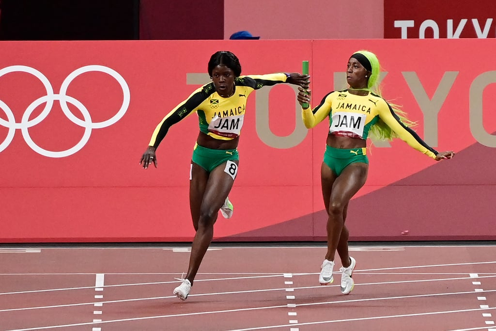Shelly-Ann Fraser-Pryce hands off the baton to Shericka Jackson as Jamaica competes in the women's 4x100m relay final at the 2021 Olympics.